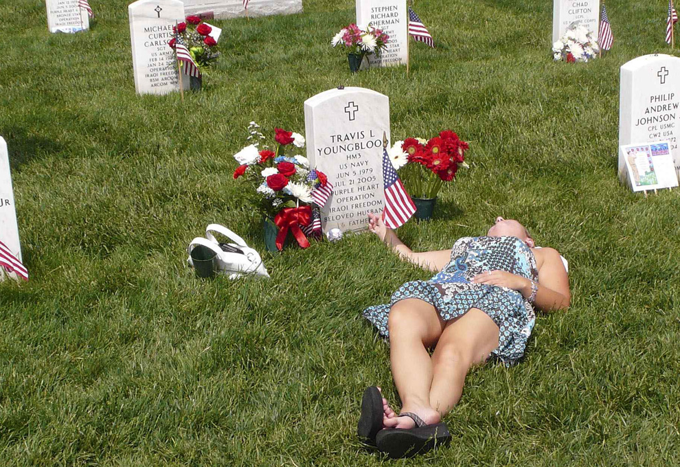 Laura Youngblood, widow of U.S. Navy Petty Officer Travis L. Youngblood, touches his gravestone while visiting his grave in Section 60 of Arlington National Cemetery during the Memorial Day weekend in Arlington, Virginia, May 24, 2009. Youngblood died of wounds received in support of Operation Iraqi Freedom in July of 2005 in Iraq. (REUTERS/Larry Downing)